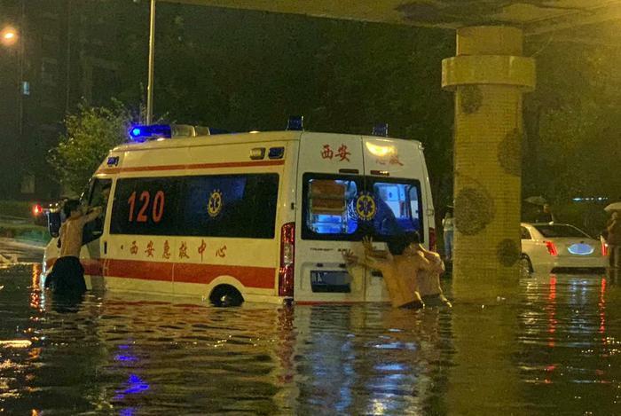 拉病人的救护车被困积水中     3名小伙徒手推车救人